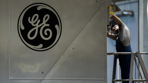 A GE logo sits on a panel as an employee works inside the General Electric Co. power plant in Veresegyhaz, Hungary, on Tuesday, June 13, 2017. General Electric won approval on Monday from the U.S. Justice Department to combine its oil and gas business with Baker Hughes Inc. Photographer: Akos Stiller/Bloomberg via Getty Images