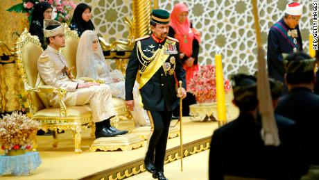 Brunei's Sultan Haji Hassanal Bolkiah (C) returns after blessing to the royal couple Princess Hajah Hafizah Sururul Bolkiah and her groom Pengiran Haji Muhammad Ruzaini (L) at the end of the sitting-in-state on royal dais ceremony at Istana Nurul Iman in Brunei's capital Bandar Seri Begawan on September 23, 2012.  Daughter of Brunei's sultan and her groom were officially presented to the royal court in a colourful ceremony in the tiny oil-rich monarchy. AFP PHOTO        (Photo credit should read STR/AFP/GettyImages)