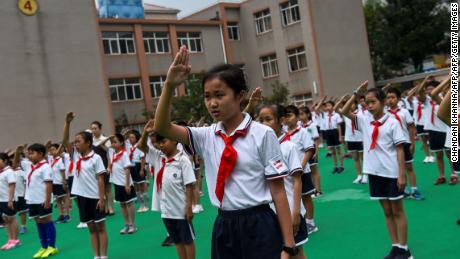 In this 2017 photograph, students sing the national anthem on the playground during the flag-hoisting ceremony at their school in Shanghai, China.