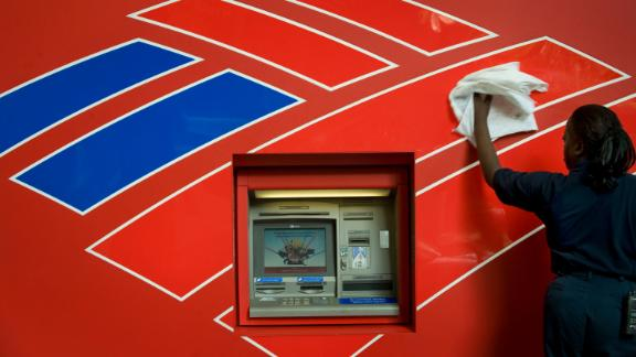 CHARLOTTE, NC - SEPTEMBER 15:  Queen Elizabeth Johnson, an employee of Redlee/SCS Group, cleans the front of an atm machine across the street from Bank of America's headquarters on September 15, 2008 in in Charlotte, North Carolina. After withdrawing from the competition to buy Lehman Brothers, Bank of America stepped in with an offer to buy Merrill Lynch for $50 billion. (Photo by Davis Turner/Getty Images)