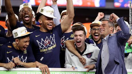 Virginia Cavaliers head coach Tony Bennett places his team's name as National Champion on the bracket after their 85-77 win over Texas Tech.