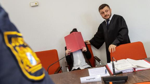 Defendant Jennifer W. hides her face behind a folder while sitting next to her lawyer Ali Aydin in court in Munich, southern Germany, on April 9, 2019.