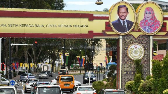 "Portraits of Brunei's Sultan Hassanal Bolkiah and Queen Saleha are seen beside a slogan (partially cutoff) in Bahasa Melayu that reads ""Obedience to Allah, loyalty to the king, love for the country"" in Bandar Seri Begawan on October 4, 2017."