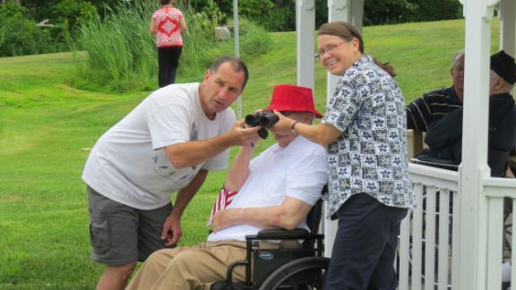 Vallieres helps a veteran spot a bird using binoculars at the New Hampshire Veterans Home.