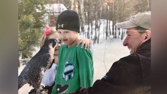 Robert Vallieres showing a peregrine falcon to boy at an Audubon camp.