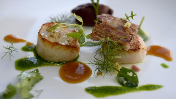 """This dish is called """"tripier marin,"""" and consists of seared scallops with black pudding and pig's feet broth garnished with glasswort and watercress."""