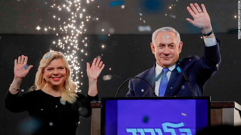 Israeli Prime Minister Benjamin Netanyahu, accompanied by his wife Sara, greets supporters.