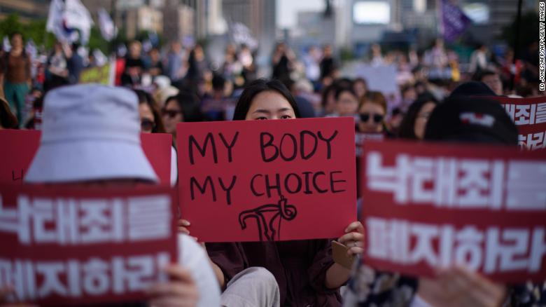 """Protesters hold placards reading """"Abolish punishment for abortion"""" as they protest South Korean abortion laws in Gwanghwamun plaza in Seoul on July 7, 2018."""