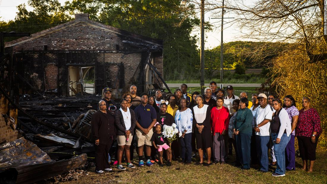 Members of the congregation of Greater Union Baptist Church stand for a portrait in front of the ruins of their former church.