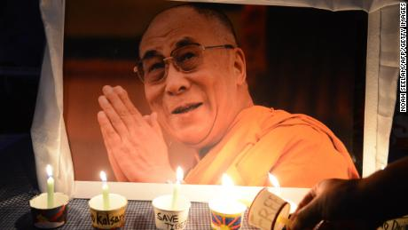 A Tibetan activist lights a candle in front of a poster of spirtual leader The Dalai Lama as members of the Regional Tibetan Youth Congress (RTYC) take part in a candlelight vigil during a protest rally in Hyderabad on March 10, 2016.