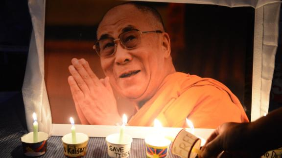 A Tibetan activist lights a candle in front of a poster of the Dalai Lama during a protest rally in Hyderabad, India, in March 2016. The rally marked the 57th anniversary of the Tibetan uprising.
