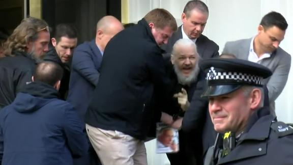 """A screen grab from video footage shows the dramatic moment when Assange was <a href=""""https://edition.cnn.com/2019/04/11/uk/julian-assange-arrested-gbr-intl/index.html"""" target=""""_blank"""">hauled out of the Ecuadorian Embassy by police</a> on April 11, 2019. Assange was arrested for """"failing to surrender to the court"""" over a warrant issued in 2012. Officers made the initial move to detain Arrange after Ecuador withdrew his asylum and invited authorities into the embassy, citing the Australian's bad behavior."""