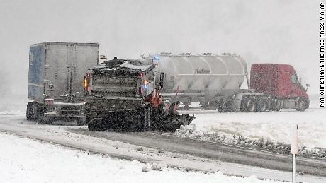 A Minnesota Department of Transportation snowplow helps a pair of semis struggling Wednesday to get up a ramp to eastbound Highway 14 from southbound Highway 169 near Mankato.