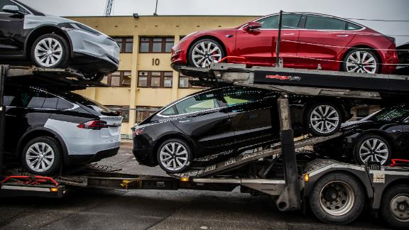 Automobiles produced by Tesla Inc. sit a car transporter truck after arriving on the Glovis Couragevehicles carrier vessel at the Port of Oslo in Oslo, Norway, on Friday, March 15, 2019. Tesla made one of the largest deliveries yet of its new Model 3 car to Norway, one of the electric-vehicle producer