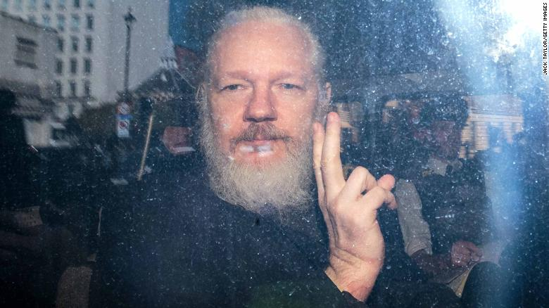 Julian Assange gestures from a police vehicle on his arrival at Westminster Magistrates' Court in London on April 11, 2019. Assange, founder of the website WikiLeaks, has been a key figure in major leaks of classified government documents, cables and videos.<br />