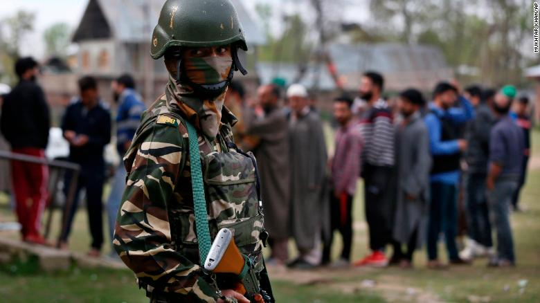 An Indian soldier guards as Kashmiri voters queue up to cast their votes outside a polling station at Shadipora, outskirts of Srinagar, in Indian-controlled Kashmir.