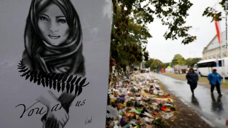 People walk past flowers and tributes displayed in memory of the twin mosque massacre victims outside the Botanical Gardens in Christchurch on April 5, 2019.