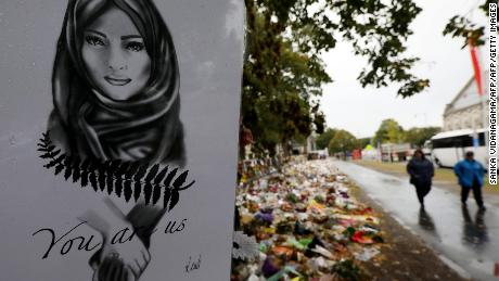 People pass by the flowers and dances displayed in memory of the victims of the mosque's massacre outside mosque outside the Botanical Garden in Christchurch on April 5, 2019