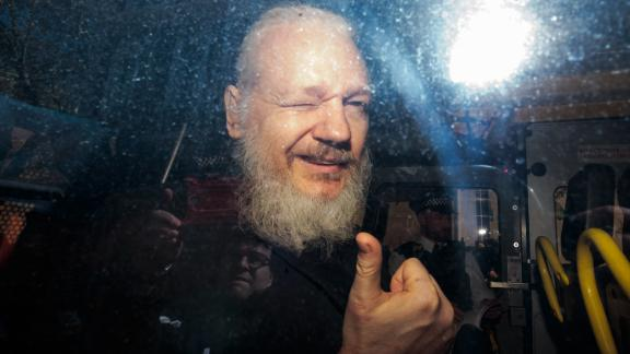 Julian Assange gestures to the media from a police vehicle on his arrival at Westminster Magistrates court on April 11, 2019 in London, England.  After weeks of speculation Wikileaks founder Julian Assange was arrested by Scotland Yard Police Officers inside the Ecuadorian Embassy in Central London this morning. Ecuador