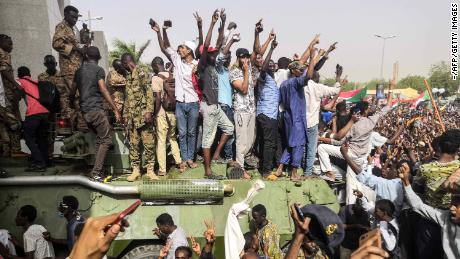 Sudanese anti-regime demonstrators stand on an army armored vehicle on April 11, 2019.