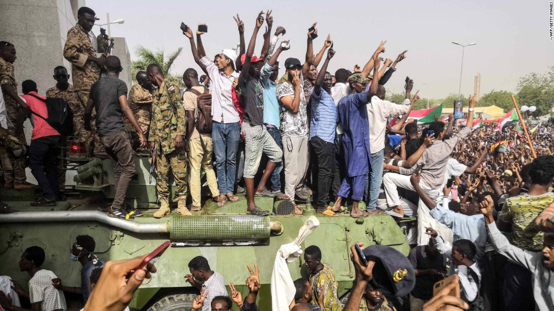 Demonstrators stand on a military vehicle in Khartoum, Sudan, cheering and flashing the sign of victory on Thursday, April 11. Sudanese President Omar al-Bashir has been arrested and forced from power in a military coup.