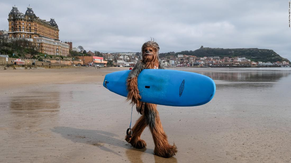 Will Hyde, wearing a Chewbacca costume, carries a surfboard across a beach in Scarborough, England, on Saturday, April 6. The town was hosting a sci-fi event over the weekend.