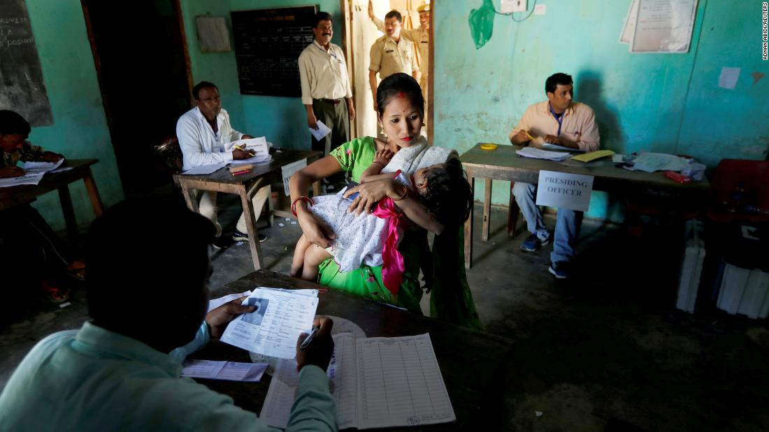 A woman struggles to hold her daughter as she waits to collect her voter slip in Majuli, India, on Thursday, April 11.