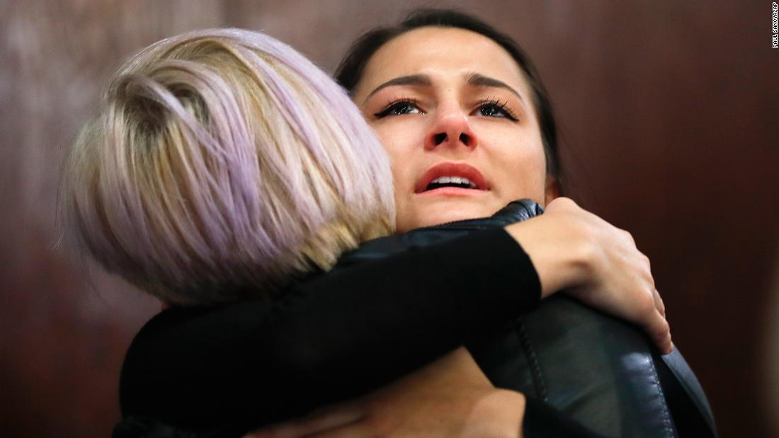 Bailey Kowalski hugs a friend after a news conference in East Lansing, Michigan, on Thursday, April 11. The 22-year-old student is speaking publicly a year after suing Michigan State University and three former basketball players who she says raped her at what was supposed to be a party in 2015.