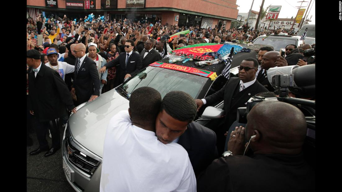 Two men hug as a hearse carrying the casket of slain rapper Nipsey Hussle passes through the crowd in Los Angeles on Thursday, April 11. Hours after thousands gathered to say goodbye to Nipsey in a memorial at Staples Center, throngs lined the streets and climbed poles Thursday night to watch the procession pass by.