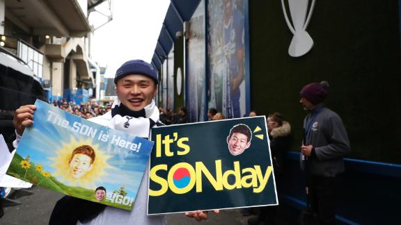 A Tottenham fan poses for a photo with his Son themed posters.