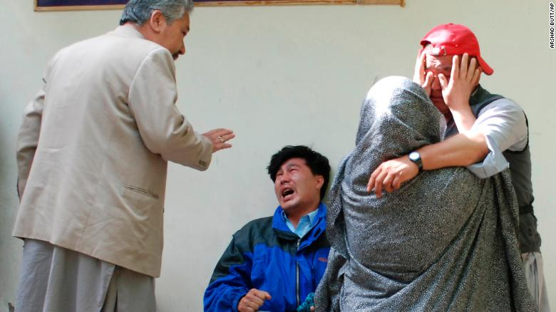 Family members of the blast victims comfort each other outside a mortuary in Quetta, Pakistan, after bomb went off at an open-air market in the southwestern city.