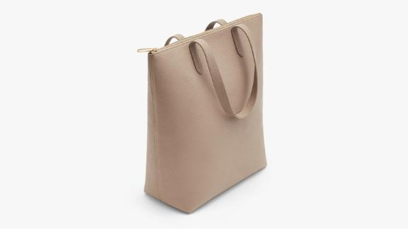 """<strong>Cuyana Tall Structured Leather Zipper Tote ($215;</strong><a href=""""http://redirect.viglink.com?type=bk&opt=false&u=https%3A%2F%2Fwww.cuyana.com%2Ftall-structured-leather-zipper-tote.html%23stone&key=ed7eb6546c416eb284920d7a87c6d8c4"""" target=""""_blank"""" target=""""_blank""""><strong> cuyana.com</strong></a><strong>)</strong><br /><br />If you're looking for a tote but are concerned about keeping your valuables safe and secure, this zipper tote from Cuyana is the one for you. It's made of beautiful Italian pebbled leather and has a built-in laptop sleeve and an internal pocket for your phone and wallet."""