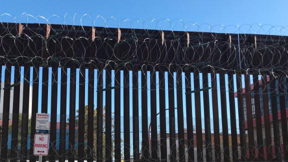 A section of the border fence with razor wire in Nogales, Arizona, looking south into Mexico.