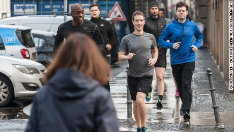 Facebook's Mark Zuckerberg runs with bodyguards in Germany in 2016.