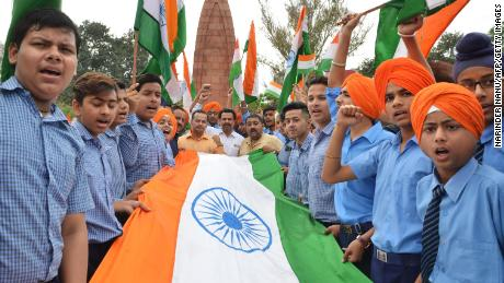Indian school students hold the national flag in honor of the Jallianwala Bagh massacre, on the eve of the anniversary.