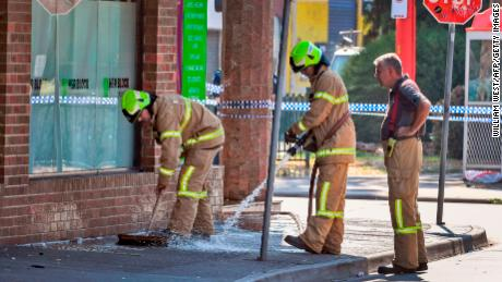 Firefighters wash away bloodstains at the scene of a deadly shooting in Melbourne, Australia.