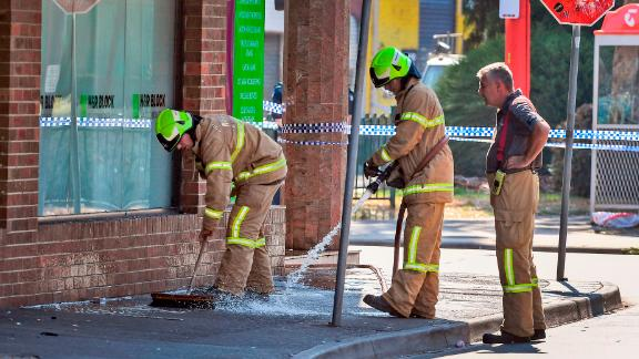 Firemen wash away bloodstains after a security guard was shot dead with another man fighting for his life after a drive-by shooting outside a popular Melbourne nightclub on April 14, 2019. - Police said four men -- three security guards and a patron waiting to get in -- were shot outside the venue in the trendy inner-city suburb of Prahran amid a spate of gun violence in Australia