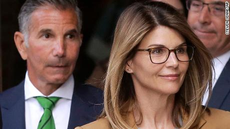 Actress Lori Loughlin, front, and husband, clothing designer Mossimo Giannulli, left, have both pleaded not guilty to two conspiracy charges in the admissions scam.