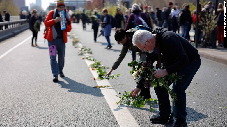 Protesters lay flowers on the road as they stage a demonstration on Waterloo Bridge.