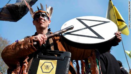 A demonstrator bangs a drum during a climate protest in London's Parliament Square.