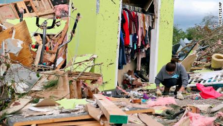 Woman in Mississippi searches for belongings in her storm-damaged house.