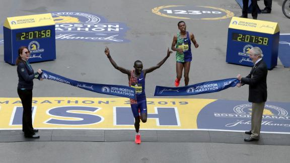 Lawrence Cherono of Kenya breaks the tape to win the 123rd Boston Marathon in front of two-time champion Lelisa Desisa of Ethiopia.