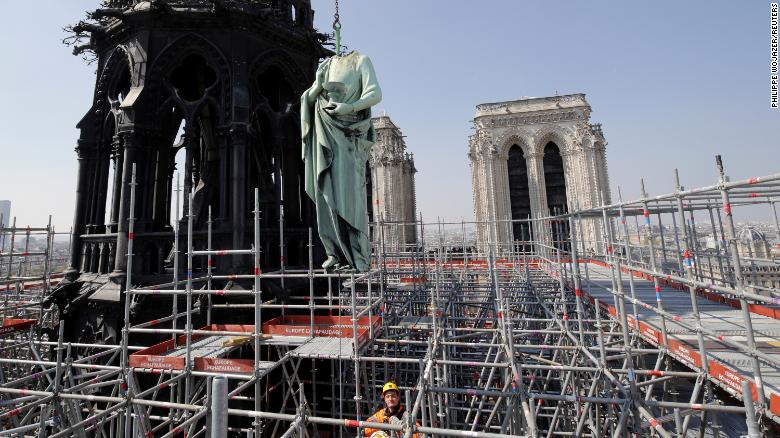 A statue of Saint John is removed from the spire of Notre Dame cathedral by a crane before restoration work, in Paris, France, April 11, 2019.