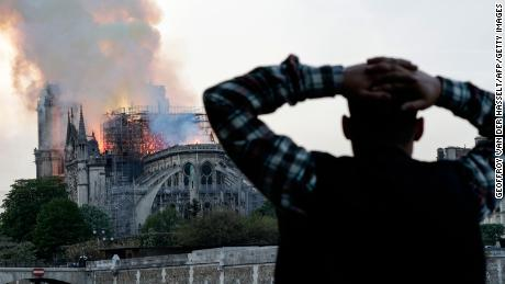 A man watches as the landmark Notre Dame cathedral is engulfed in flames.