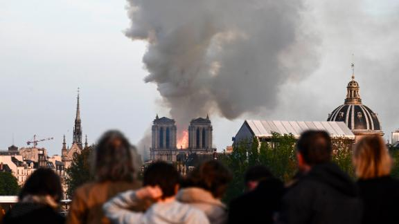 """Passers-by watch the cathedral burn. """"It's tremendously sad to see this happening to such an iconic monument,"""" bystander Cameron Mitchell <a href=""""https://www.cnn.com/world/live-news/notre-dame-fire/h_f0e87d76f5c736f2e79dffdf7e363b01"""" target=""""_blank"""">told CNN.</a>"""