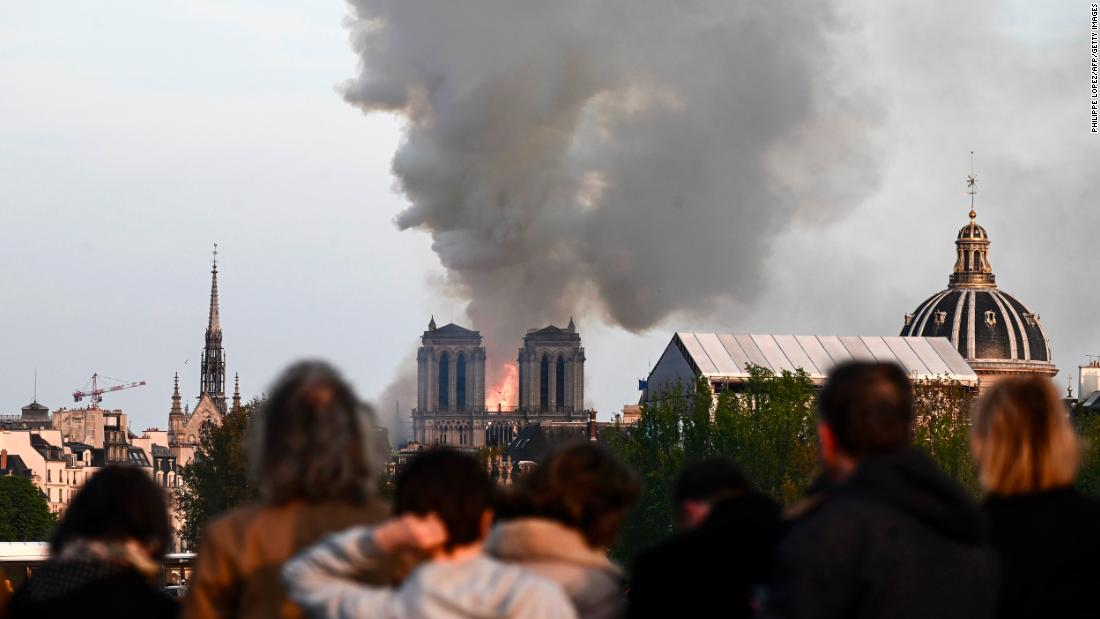 "Passers-by watch the cathedral burn. ""It's tremendously sad to see this happening to such an iconic monument,"" bystander Cameron Mitchell <a href=""https://www.cnn.com/world/live-news/notre-dame-fire/h_f0e87d76f5c736f2e79dffdf7e363b01"" target=""_blank"">told CNN.</a>"