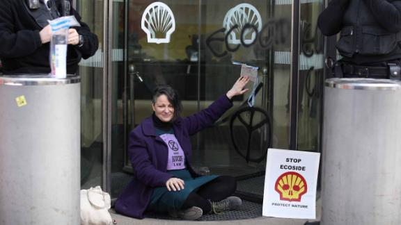A campaigner sits with her hand glued to the revolving doors at the entrance to the Shell Oil building on April 15.