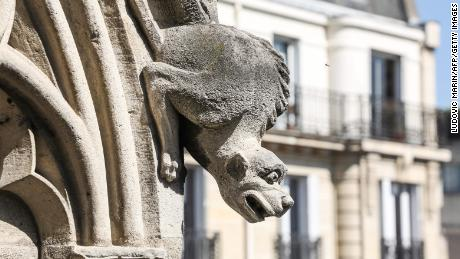 A distressed gargoyle adorns the exterior of Notre Dame Cathedral.