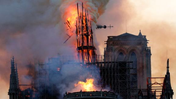 The steeple collapses as smoke and flames engulf the Notre-Dame Cathedral in Paris on April 15, 2019. - A huge fire swept through the roof of the famed Notre-Dame Cathedral in central Paris on April 15, 2019, sending flames and huge clouds of grey smoke billowing into the sky. The flames and smoke plumed from the spire and roof of the gothic cathedral, visited by millions of people a year. A spokesman for the cathedral told AFP that the wooden structure supporting the roof was being gutted by the blaze. (Photo by Geoffroy VAN DER HASSELT / AFP)        (Photo credit should read GEOFFROY VAN DER HASSELT/AFP/Getty Images)