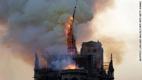 The steeple of the landmark Notre Dame cathedral collapses as the cathedral is engulfed in flames in central Paris.